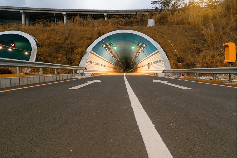 An asphalt road leading into a tunnel in a hill