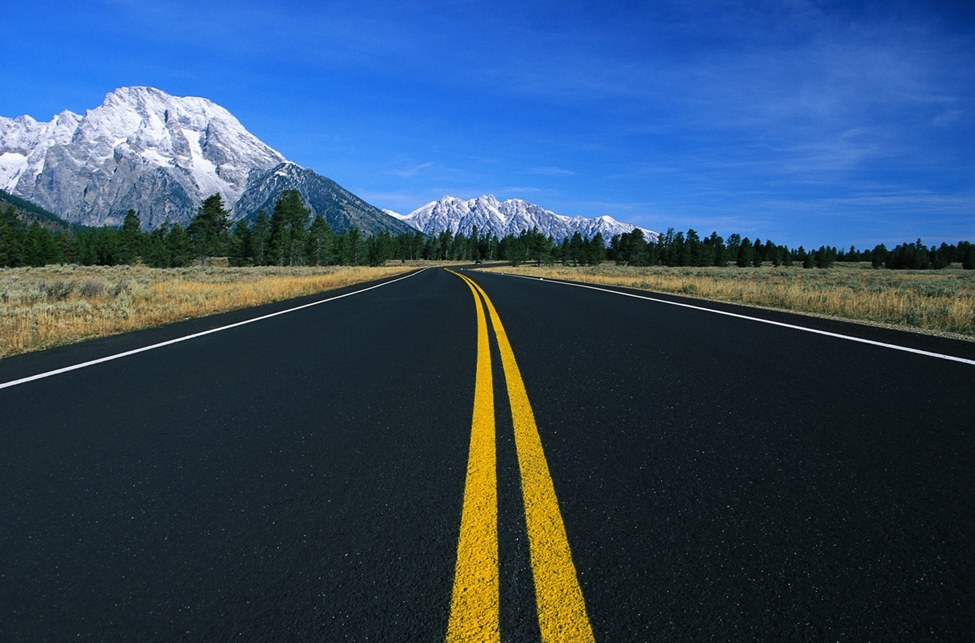 Freshly paved road set against pine trees and snow-topped mountains