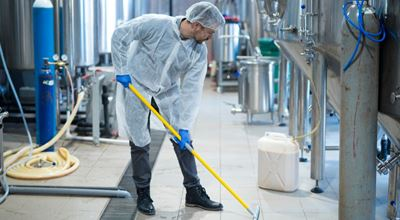 Professional industrial cleaner in protective uniform cleaning floor of food processing plant. Achieve remarkable heavy-duty cleansing, degreasing and disinfectant performance from Nouryon's extensive portfolio of products – ranging from high alkaline, solvent and acid-based formulations to all-purpose hard surface cleaners