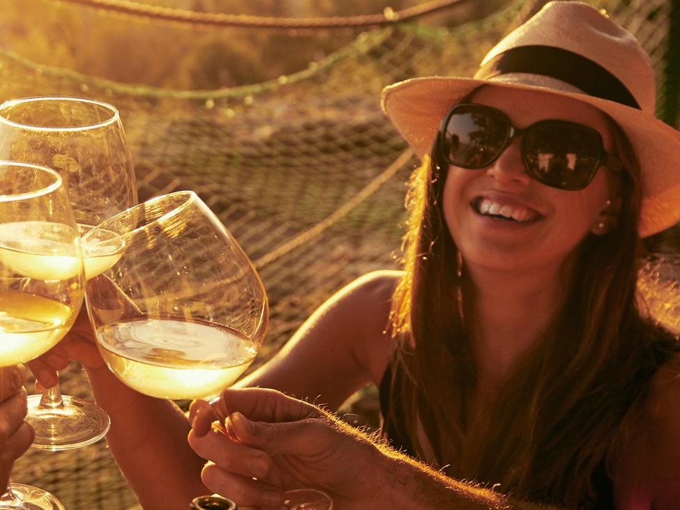 Woman enjoying white wine with friends. Expancel Microspheres is an excellent additive in micro-agglomerated and synthetic wine corks.