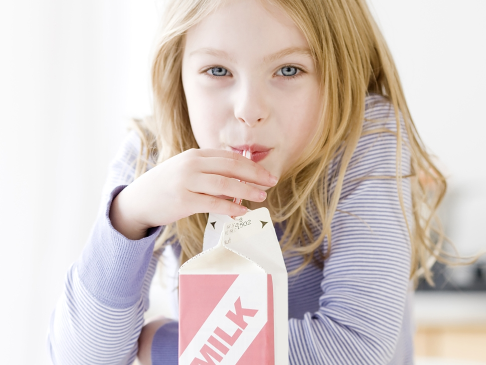Girl drinking milk from a cardboard milk container. Levasil Colloidal Silica is used to enhance the frictional and printing properties of board stock.
