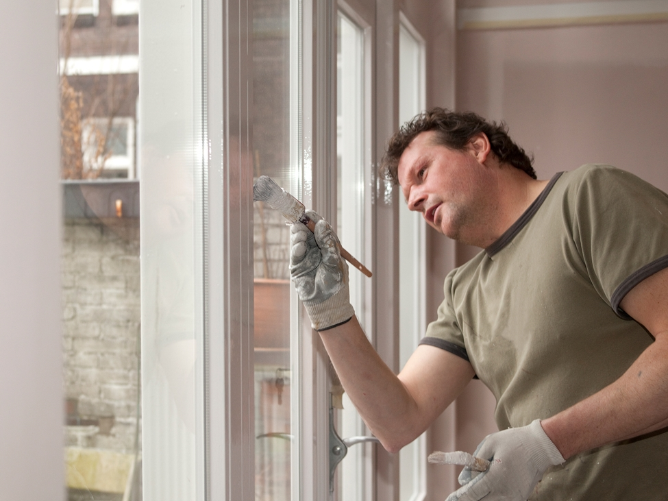 Man painting a window frame in white. The so-called open time of a paint is what allows you to go back and make final touches without getting unwanted stroke marks, Levasil colloidal silica can be added to a paint formulation to improve open time.